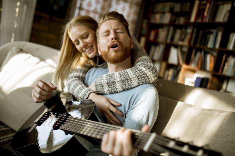 Человек играя акустическую гитару на софе для его молодой красивой женщины стоковое изображение