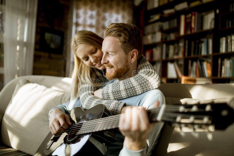 Человек играя акустическую гитару на софе для его молодой красивой женщины стоковые фото