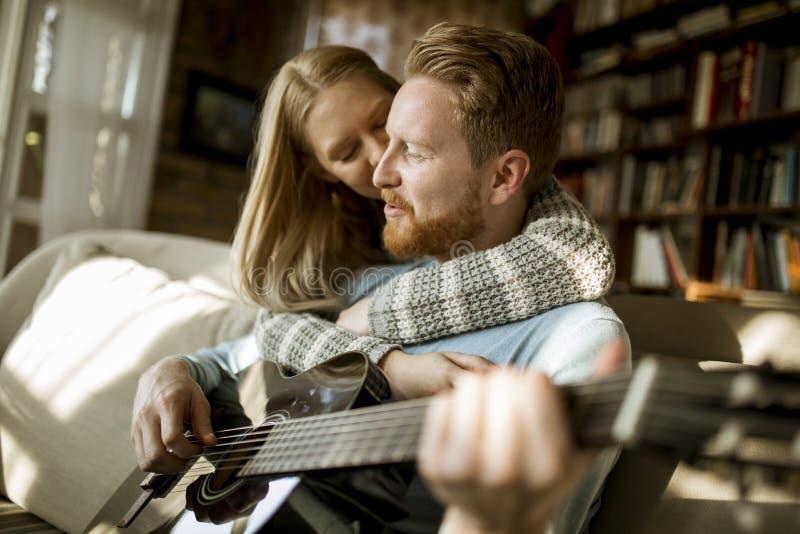 Человек играя акустическую гитару на софе для его молодой красивой женщины стоковая фотография