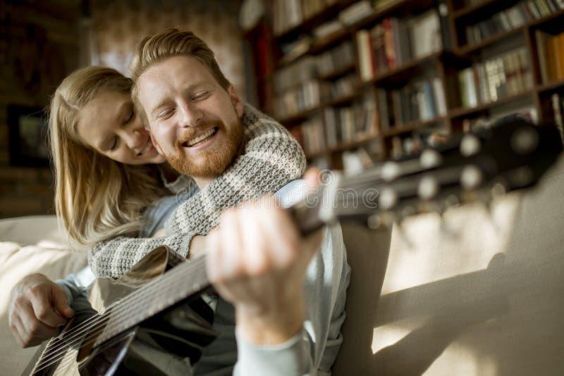 Человек играя акустическую гитару на софе для молодой красивой женщины стоковая фотография rf