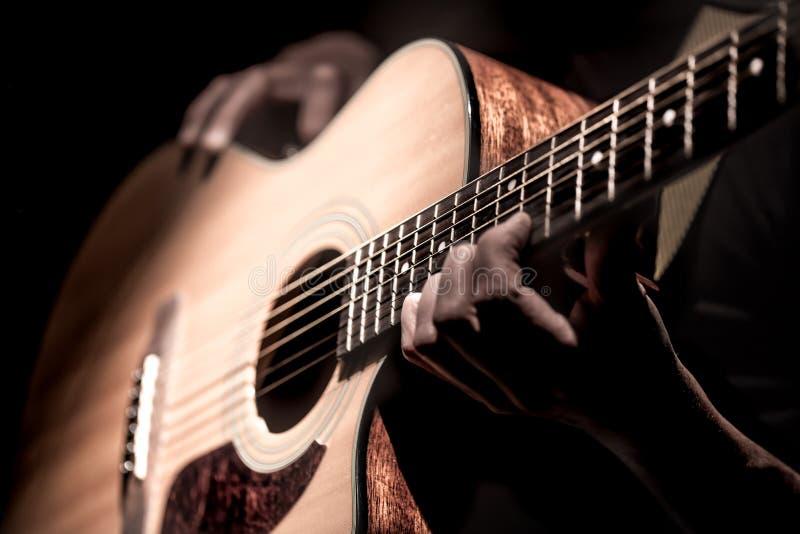 Человек играя акустическую гитару на темной предпосылке Музыкальная концепция стоковая фотография rf