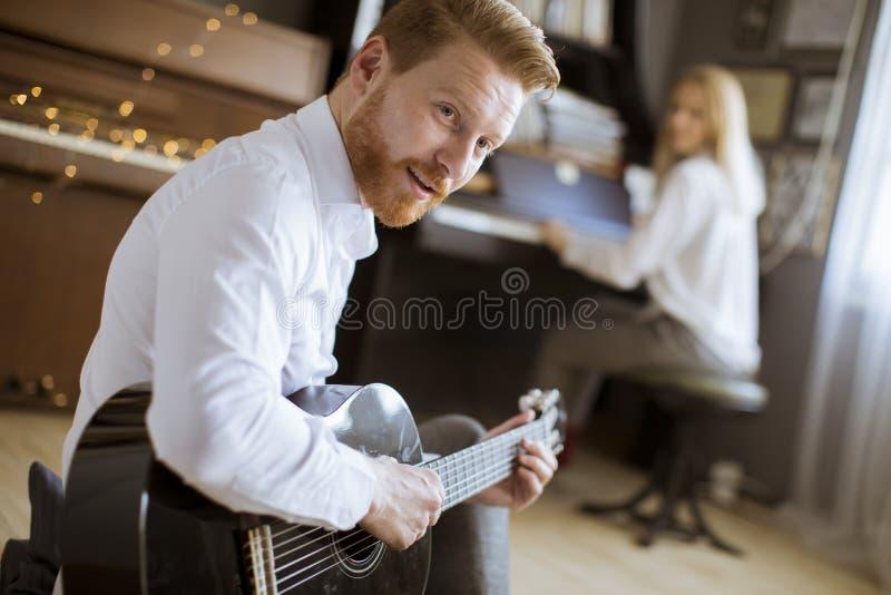 Человек играя акустическую гитару с красивой женщиной которая играет рояль стоковое изображение