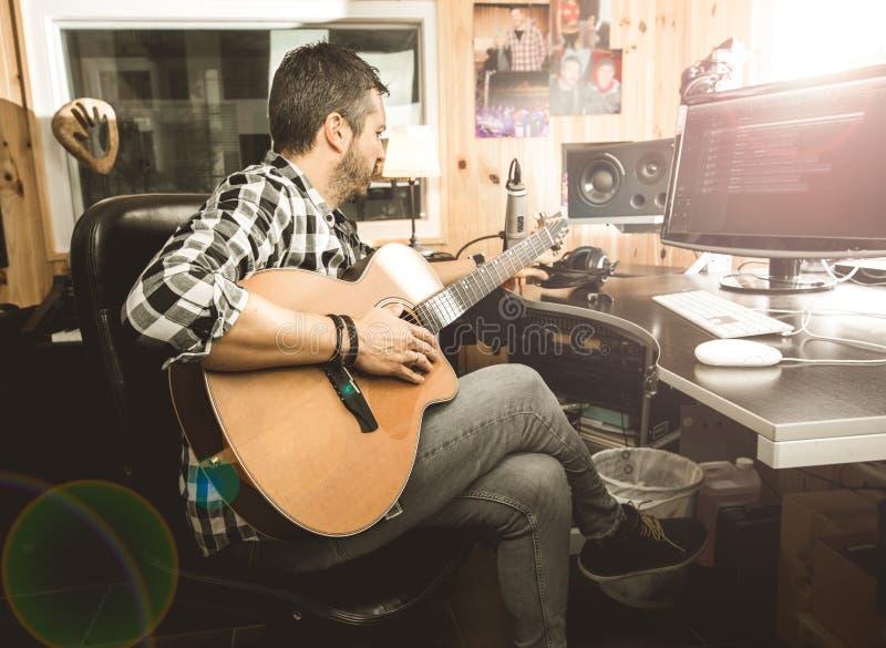 Человек играя гитару в студии звукозаписи Музыка гитариста концепции составляя стоковая фотография rf