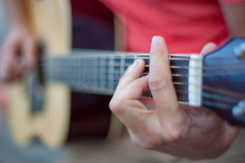 Человек играя гитару, конец вверх стоковое изображение rf