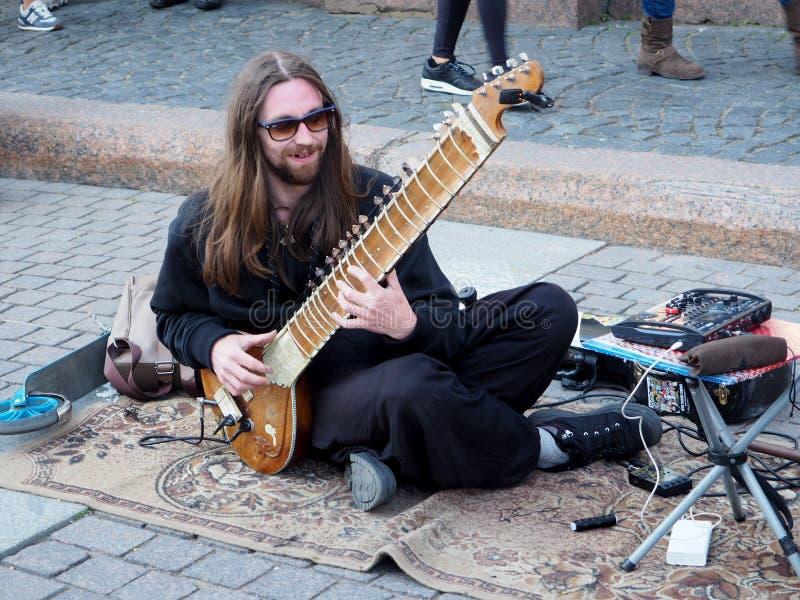 Человек играя гитару на улице города стоковые фото