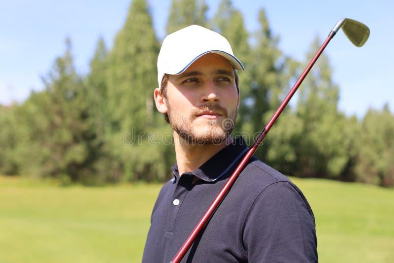 Человек играя гольф на красивом солнечном зеленом поле для гольфа стоковое изображение