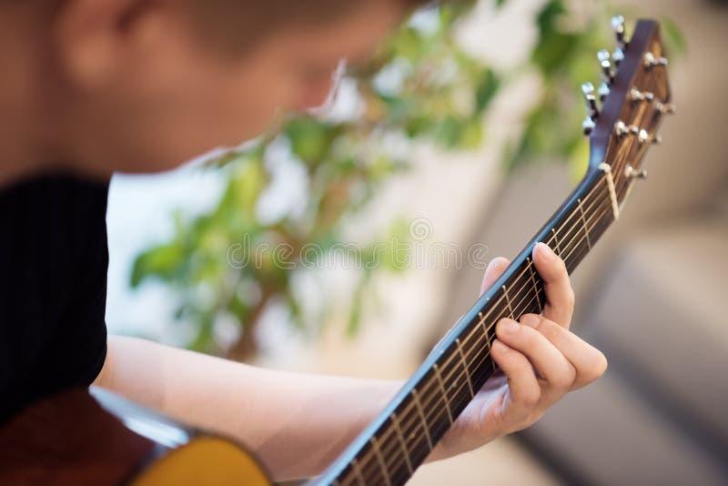 Человек играя крупный план акустической гитары учить нот стоковое изображение