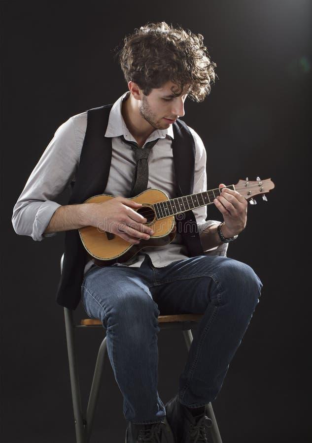 человек играя сидя детенышей ukulele стоковое фото rf