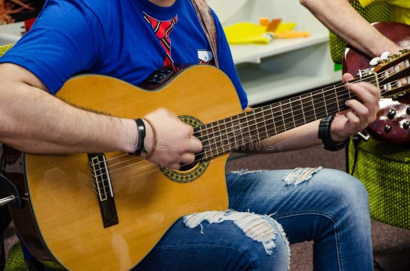 Человек играя усиленную акустическую гитару стоковое изображение