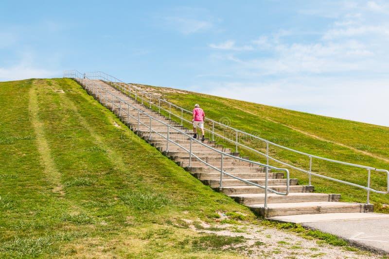 Человек идет вверх по шагам на держатель Trashmore стоковые изображения rf