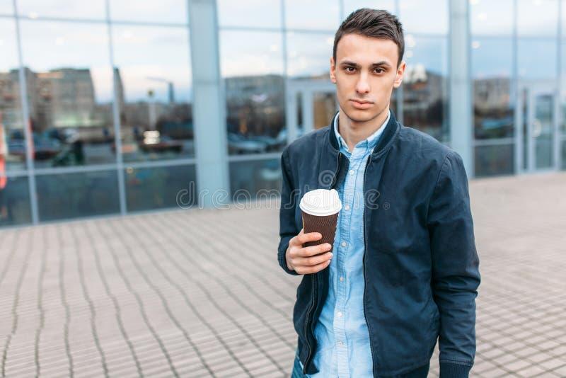 Человек идет вокруг города и выпивая кофе от бумажного стаканчика, красивый парень идет вокруг и отдыхающ, парень на backgrou стоковые изображения