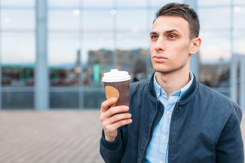 Человек идет вокруг города и выпивая кофе от бумажного стаканчика, красивый парень идет вокруг и отдыхающ, парень на backgrou стоковые фотографии rf