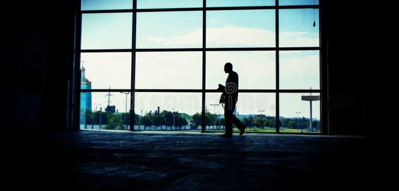 Человек идет против окна в комнате Запрет панорамных и сети стоковые фото