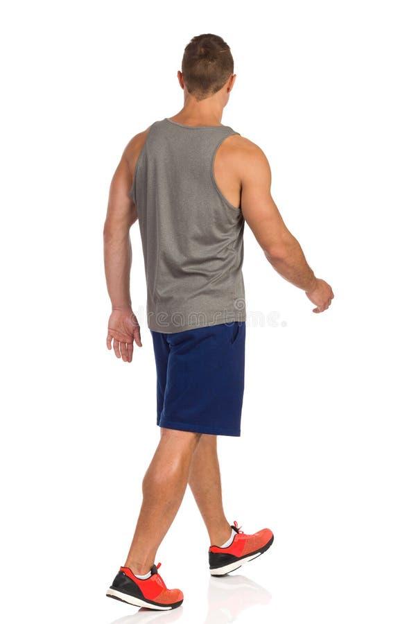 Человек идя в одежды спорта задний взгляд со стороны изолировано стоковые фото