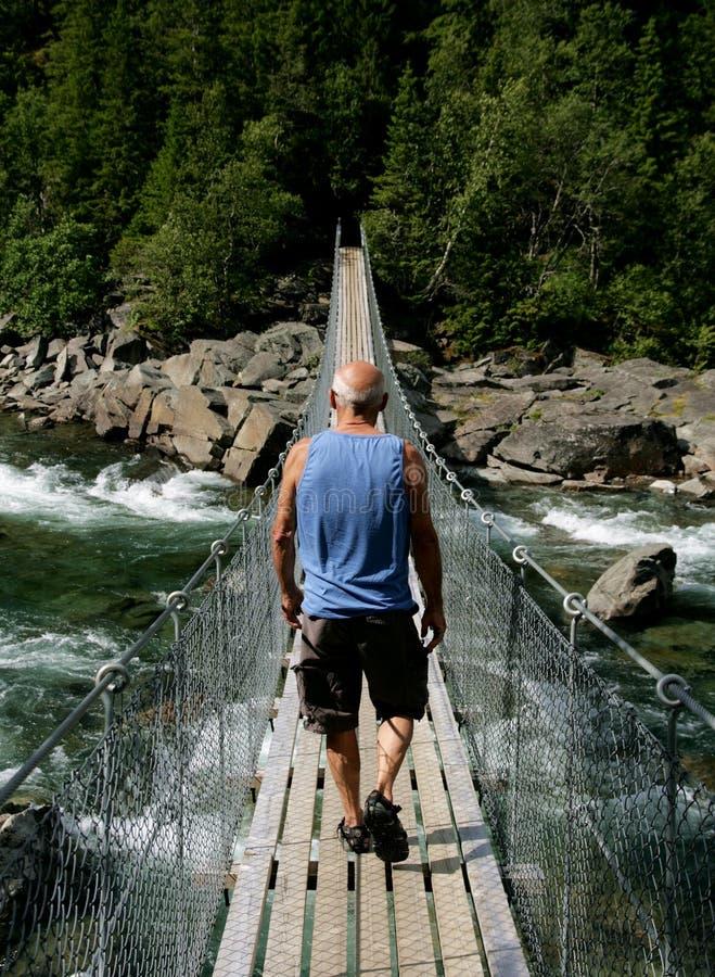 Человек идя над висячим мостом стоковое фото rf