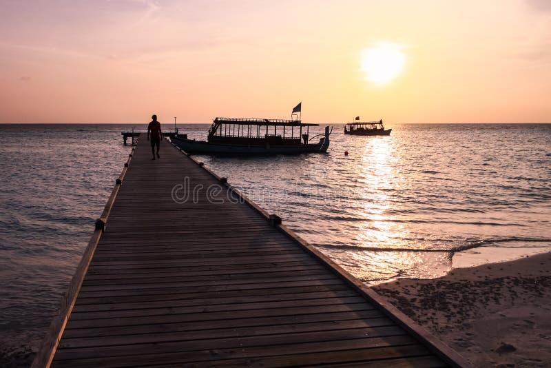Человек идя на пристань на заходе солнца в островном курорте Мальдивов стоковое фото rf
