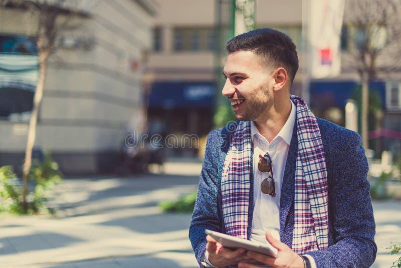 Человек идя на улицу с планшетом и усмехаться стоковая фотография rf