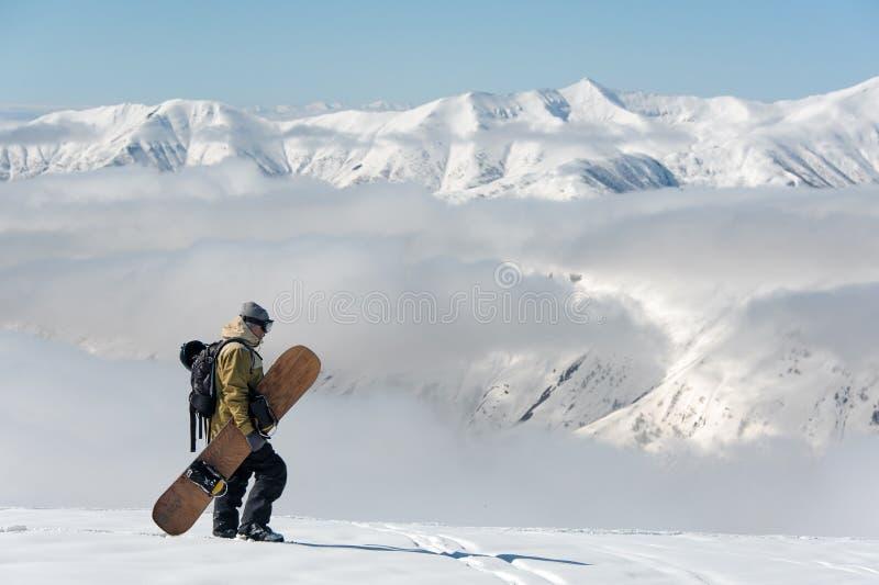Человек идя с коричневым сноубордом в горнолыжном курорте стоковые фотографии rf