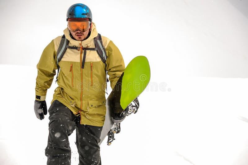 Человек идя с черным и зеленым сноубордом в горе r стоковые фото
