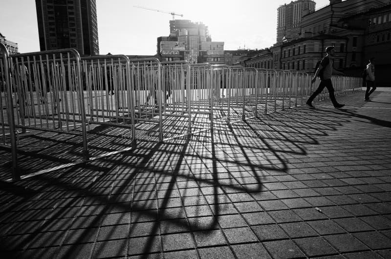 Человек идя через металлические турникеты в черно-белых цветах стоковая фотография rf