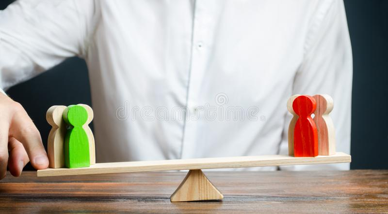 Человек изменяет баланс масштабов в пользу зеленой группы людей Обслуживания посредника Конфликт, разрешение спора, судебное стоковая фотография rf