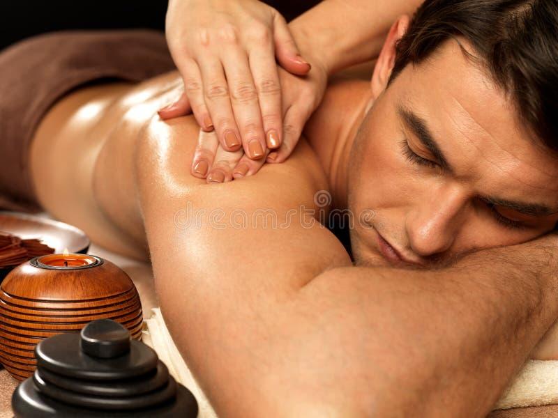 Человек имея массаж в салоне спы стоковое изображение rf