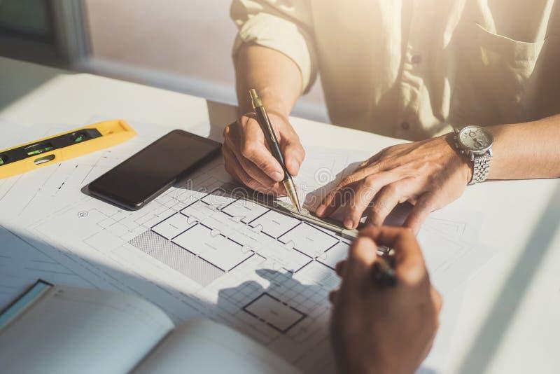 Человек инженера работая с осмотром чертежей в рабочем месте в офисе Концепция инструментов и конструкции инженерства Архитектор  стоковое фото