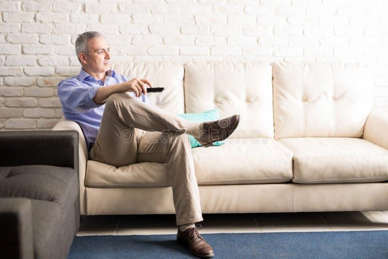 Человек испанца зрелый смотря ТВ дома стоковые фотографии rf