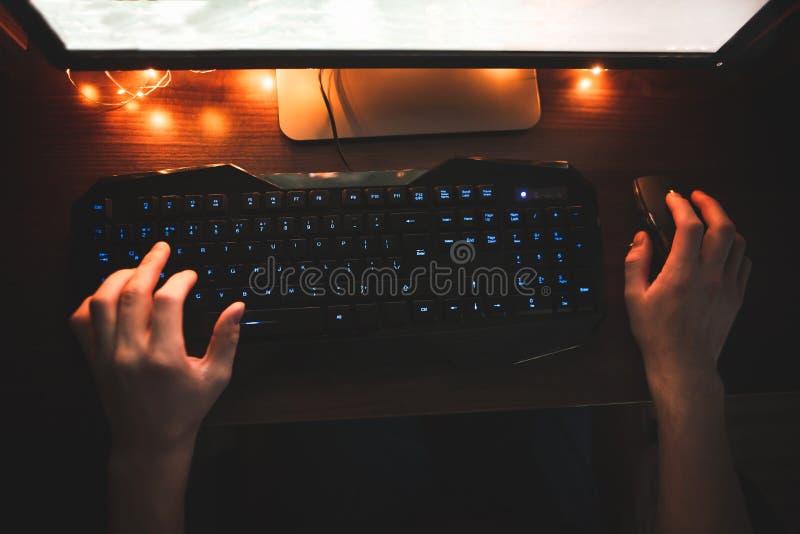 Человек использует компьютер вечером, руки на клавиатуре и мышь над верхней частью Игрок игры мыши и клавиатуры стоковая фотография rf