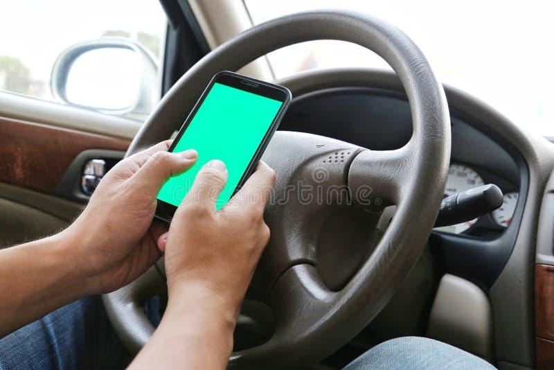 Человек используя его мобильный телефон пока управляющ опасный водитель Экран голубых/зеленого цвета стоковая фотография rf