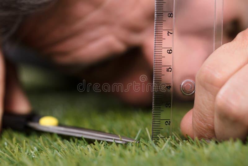 Человек используя измеряя масштаб пока режущ траву стоковое фото rf