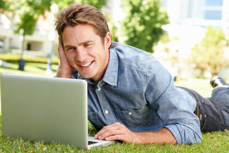 Человек используя компьтер-книжку в парке города стоковые изображения