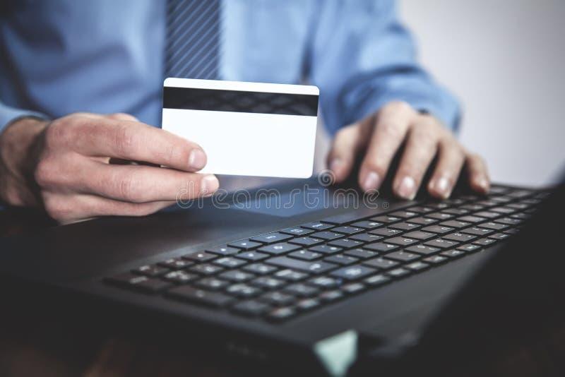 Человек используя компьтер-книжку и показывающ кредитную карточку владение домашнего ключа принципиальной схемы дела золотистое д стоковое изображение rf