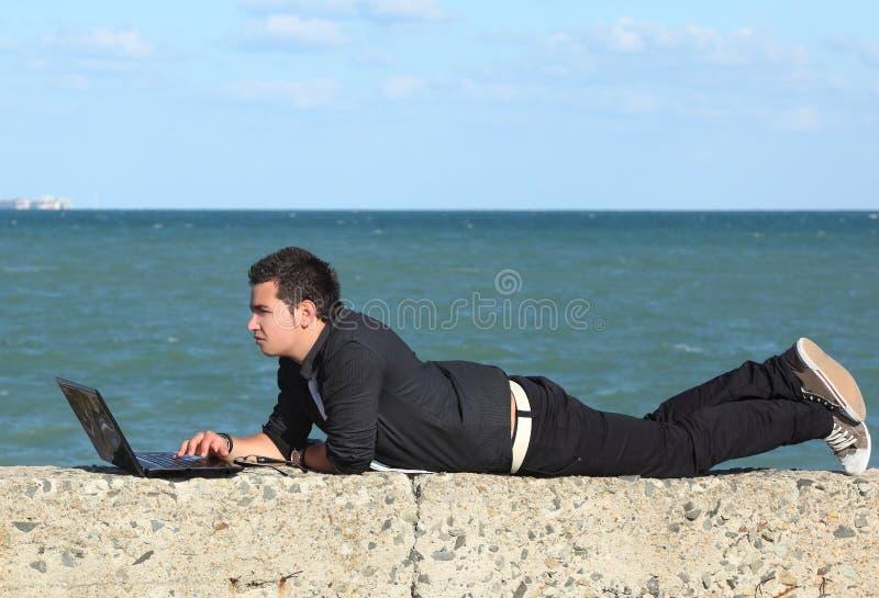 Человек используя компьтер-книжку и телефон на пляже стоковая фотография rf