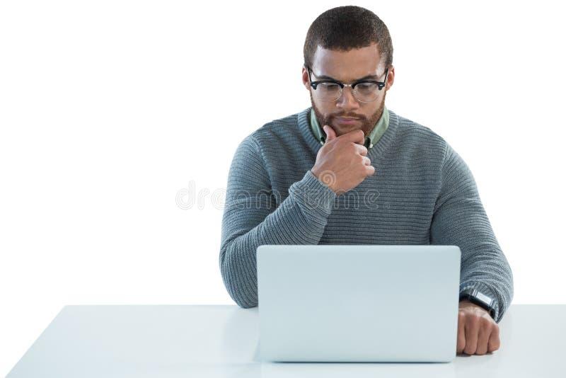 Человек используя компьтер-книжку против белой предпосылки стоковые фото