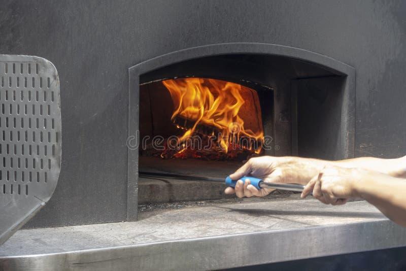 Человек используя корку пиццы металла к варить выпечку outdoors в стальной деревянной горящей печи для хлеба etc пиццы стоковые фото
