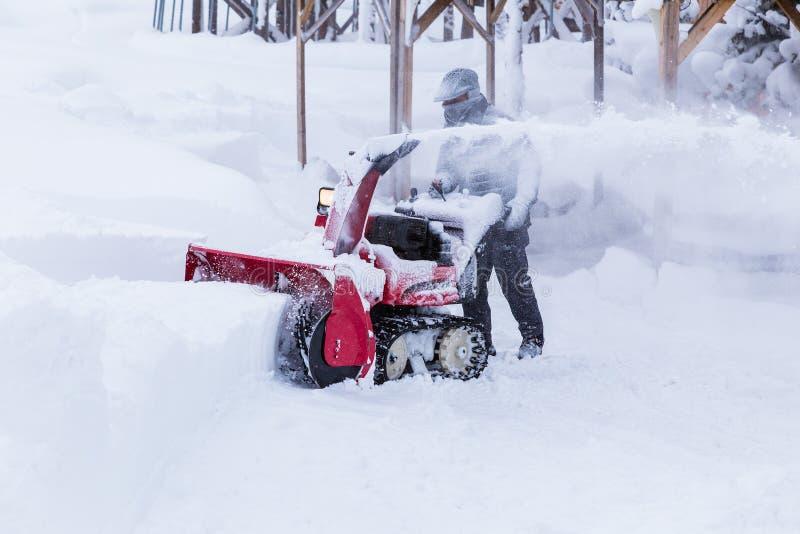 Человек используя машину удаления снега стоковые изображения rf