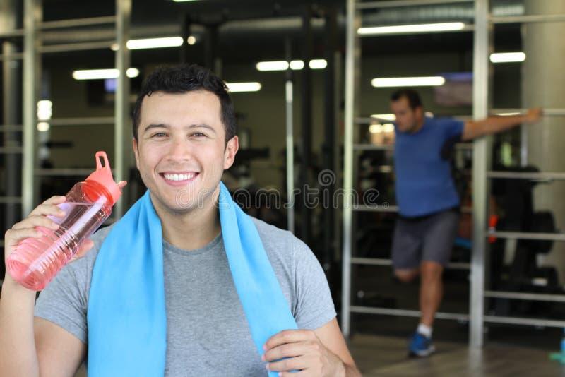 Человек используя многоразовую пластиковую бутылку с водой на спортзале стоковые фотографии rf