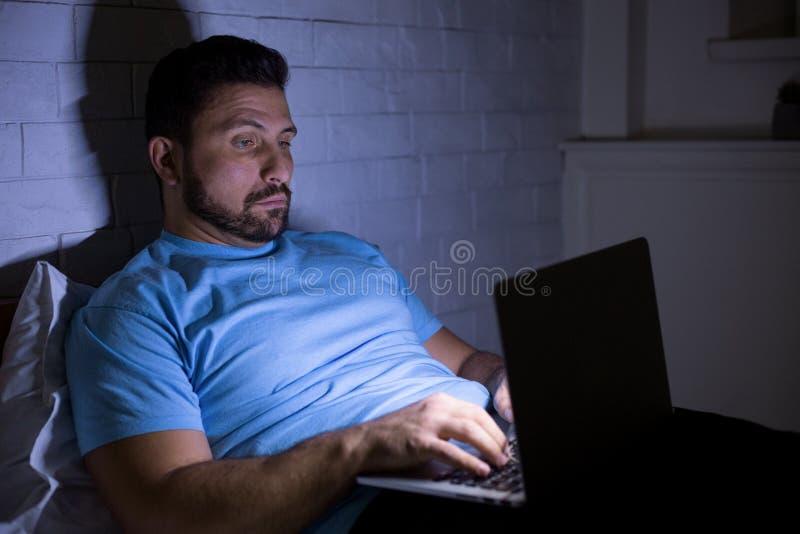 Человек используя ноутбук делая тяжелую работу вечером стоковая фотография rf
