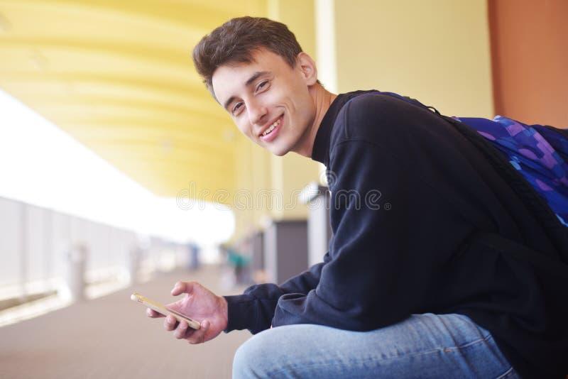 Человек используя передвижное применение на его smartphone на вокзале, перемещении Красивый в железнодорожном вокзале Человек улы стоковая фотография rf