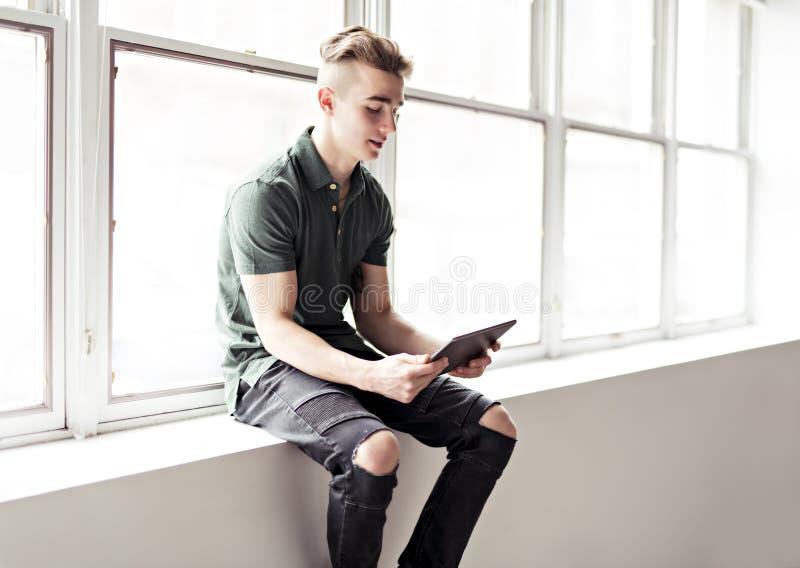 Человек используя планшет сидеть ont граница окна стоковое изображение rf