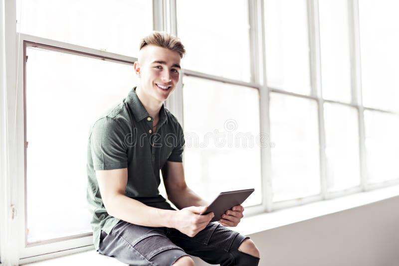 Человек используя планшет сидеть ont граница окна стоковые изображения rf