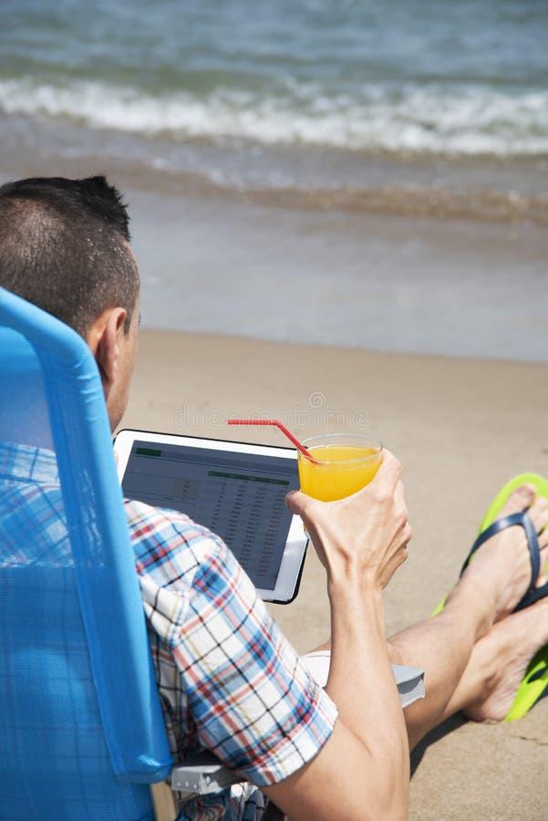 Человек используя таблетку на пляже стоковые фото