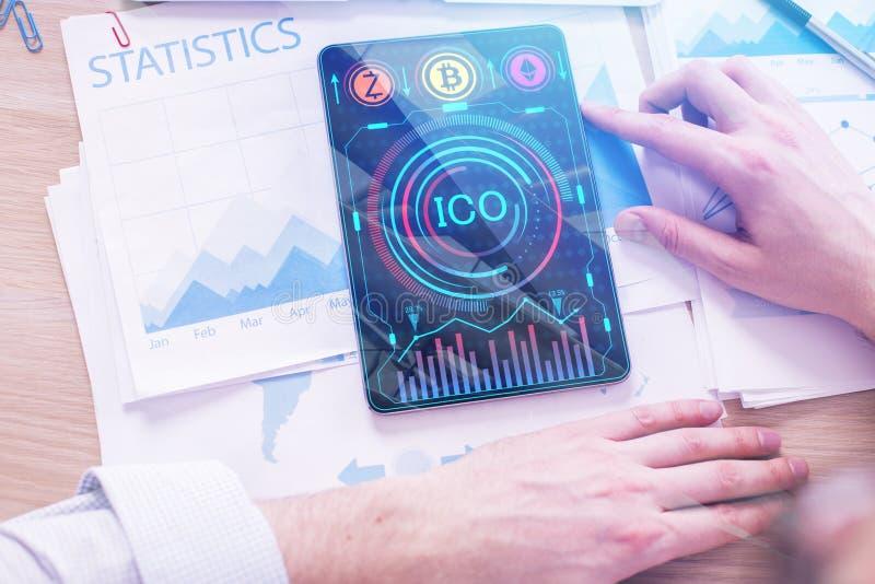 Человек используя таблетку с диаграммой ICO стоковое фото