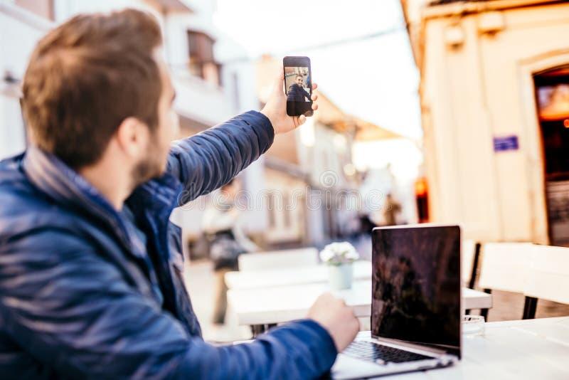 Человек используя технологию смартфона в обычной жизни, принимая selfies стоковая фотография rf