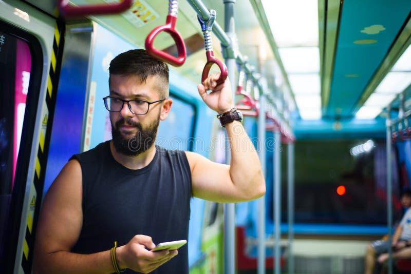 Человек используя умный телефон пока принимающ метро стоковое изображение rf
