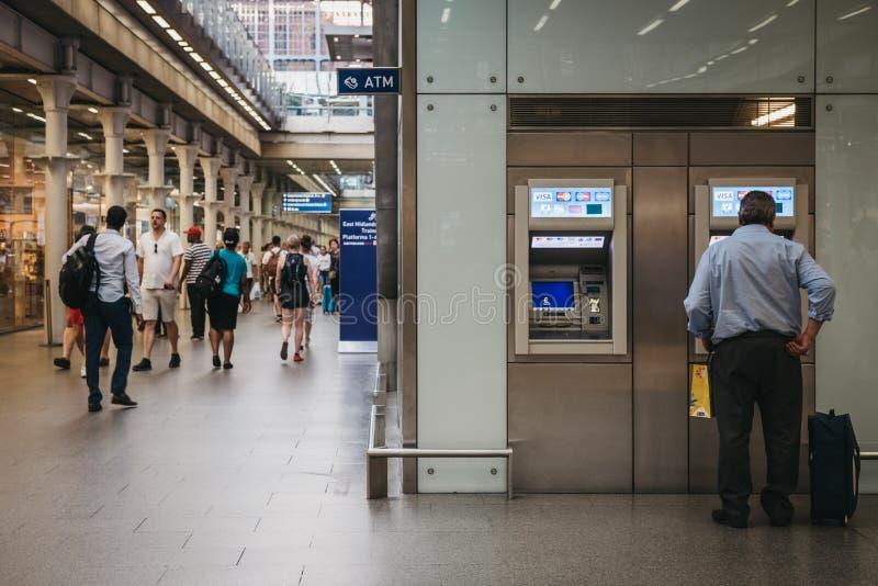 Человек используя ATM внутри станции St Pancras, Лондона, Великобритании стоковая фотография rf