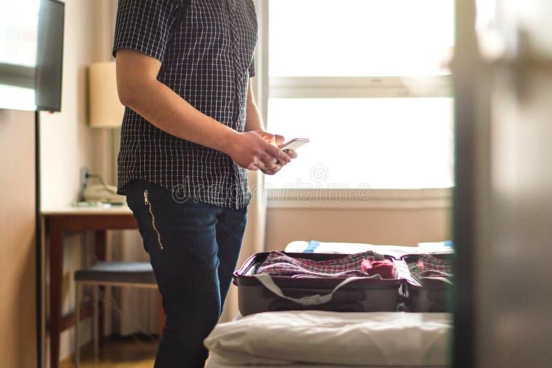 Человек используя smartphone в гостиничном номере с открытым багажем стоковая фотография