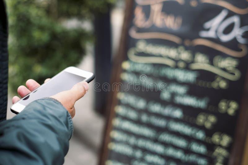 Человек используя smartphone перед рестораном стоковое изображение rf