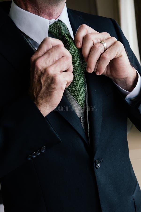Человек исправляет связь в костюме стоковое фото rf